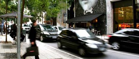 Rua de comércio repleta de lojas de grife em ambos os lados. À esquerda, em uma calçada bastante larga, plana e ornada por algumas árvores, várias pessoas caminham, algumas portando sacolas de compras. À direita, vários carros trafegam pela rua.