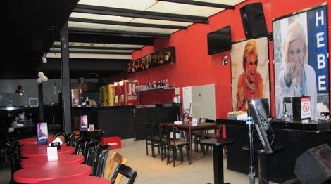 À esquerda, lado a lado, pequenas mesas redondas e vermelhas com cadeiras em madeira escura. À direita, presas em uma parede toda vermelha, uma grande TV de Led, uma robusta caixa de som e duas grandes fotografias da apresentadora Hebe Camargo. Ao fundo, bar com balcão todo preto.