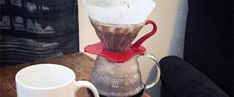 Imagem em close up. À esquerda, caneca toda branca e vazia. À direita, jarra de café toda de vidro transparente com um pouco de café no fundo. No topo da jarra, um coador de café também de vidro com uma base vermelha.