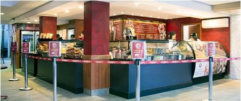 Imagem interna da sorveteria. No 1º plano, os balcões frontal e lateral em azul escuro e, sobre eles, um compartimento refrigerado de vidro com dezenas de potes de sorvetes. Ao fundo, 2 grandes cardápios nas paredes, com fundo vermelho e letras em amarelo.