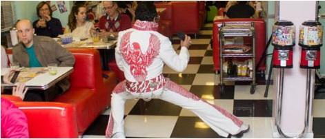 Ambiente no estilo Anos 50. À esquerda, fileiras de sofás duplos vermelhos, com mesas no centro, onde estão várias pessoas comendo. No centro, um ator cover de Elvis Presley faz uma performance sobre um piso quadriculado preto e branco. À direita, duas máquinas de chicletes.