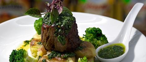 """Imagem em close up. Sobre um prato muito branco, um filé bem alto e redondo sobre batatas cozidas e amassadas e coberto por um espesso molho verde escuro e algumas folhas. Ao redor, brócolis e um recipiente de louça branca com molho """"Mint Sauce""""."""
