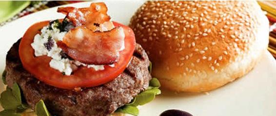 Imagem em close up. Sanduíche aberto com um grosso hambúrguer sobre uma folha de alface, coberto com uma grande fatia de tomate, queijo cottage e bacon. Do lado direito, a metade de cima de um pão coberto por gergelim.