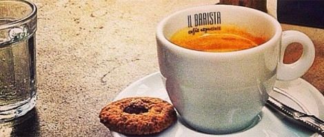 Imagem em close up. Xícara com café expresso, toda branca sobre um pires da mesma cor, uma pequena colher prateada e um biscoitinho sobre ele. Do lado esquerdo, um copinho de água com gás.