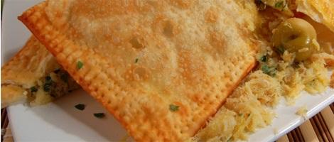 Imagem em close up de um pastel partido ao meio sobre um prato branco, com parte do recheio de bacalhau desfiado espalhado no prato.
