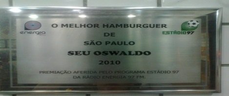 """Placa de vidro retangular com moldura prateada, onde está escrito em um fundo fosco """"O MELHOR HAMBURGUER DE SÃO PAULO"""", abaixo """"SEU OSWALDO"""", abaixo """"2010"""", abaixo """"PREMIAÇÃO AFERIDA PELO PROGRAMA ESTÁDIO 97 DA RÁDIO ENERGIA 97 FM""""."""