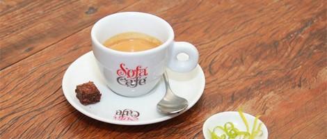 Imagem em close up. Pequena xícara com café com expresso, toda branca sobre um pires da mesma cor, uma pequena colher prateada e um biscoitinho sobre ele. Do lado direito, um pequeno pote com raspas de limão.