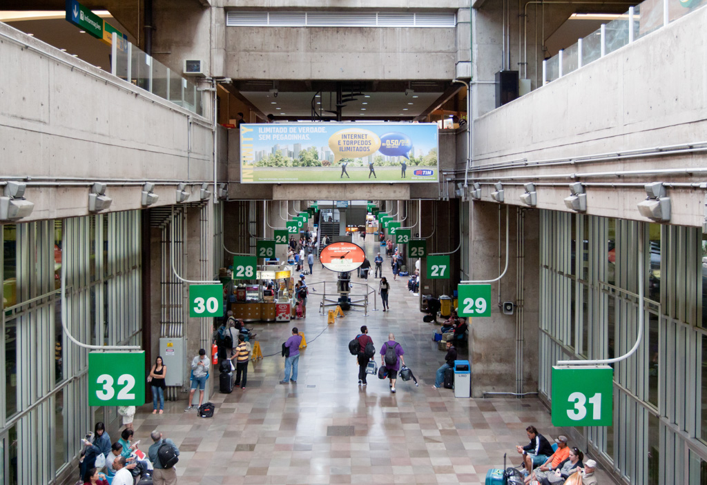 Internal photo of the Terminal. Concrete structure with 2 floors. On the first floor, a corridor with several people, quite wide, access to several boarding gates, all with a green plaque numbered in white - odd gates to the right and pairs to the left, decreasingly, from the numbers 32, 31 , 30, etc.