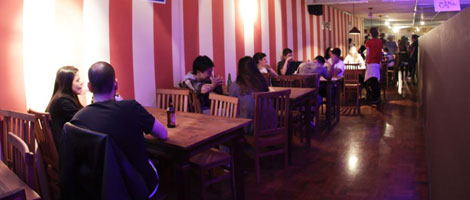 Salão com diversas pessoas sentadas comendo e bebendo, em várias mesas e cadeiras de madeira encostadas em uma parede com grossas listras verticais, vermelhas e brancas.