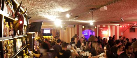Do lado direito, dezenas de pessoas comendo e bebendo, sentadas junto ao balcão do bar e diversas mesas. Do lado esquerdo, alguns barmen trabalham entre o balcão e várias prateleiras repletas de garrafas de bebidas.