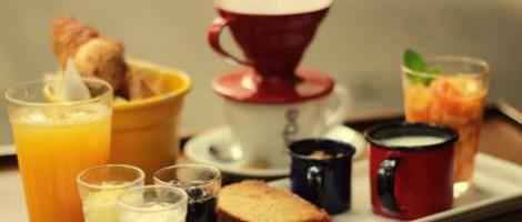 À esquerda, copo com suco de laranja e uma cesta de pães atrás. No centro, uma xícara preta esmaltada com café, outra vermelha com leite e um copo com salada de frutas. Atrás, uma xícara, toda branca sobre um pires da mesma cor, uma pequena colher prateada. No topo, um coador de café também de vidro com uma base vermelha.