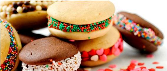 """Imagem em close up. Pequenos doces do tipo """"Macarons"""", brancos e escuros, com variados recheios multicoloridos."""