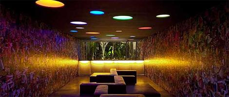 Ambiente com luz amena, paredes laterais decoradas com milhares de capas de revistas de rock, grande janela de vidro na parede do fundo dá vista para um jardim todo iluminado. No chão, bancos estreitos de couro sem encosto. No teto escuro, várias luminárias embutidas formando diversos círculos multicoloridos.