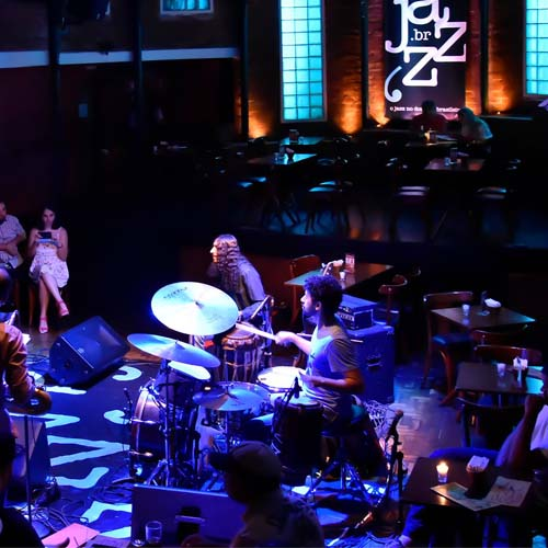 """To the left, small audience sitting around several small tables. To the right, 4 musicians present a show, all lit by spotlights of colored lights. In the background, in a wall of apparent bricks, in a large black poster is written in a stylized """"JAZZ.BR"""" in white letters, flanked by bright light blue panels."""