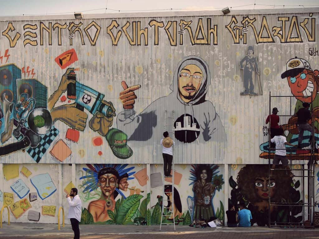 A large mural with approximately 10 meters of height by 15 meters of length, 6 street artists, part in the ground another part in the top of a metallic structure, design diverse multicolored graffiti.