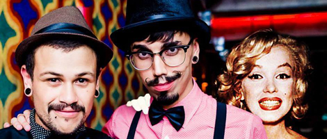 Image of the 2 artists from the neck up. The one on the left has a very thin mustache and beard, he wears a brown hat and pair of earrings. The one on the right has a dark mustache and goatee, wears glasses, a black hat, and a pair of earrings. Behind him, right next to his left shoulder, a very clear picture of the face of a blond woman with very red lips in a big smile, much like the actress Marilyn Monroe, gives the clear impression that she is real.