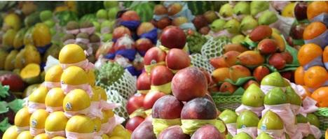 Imagem em close up. Diversas frutas arrumadas em pilhas no formato de pirâmides. São peras, uvas, maças, laranjas e goiabas.