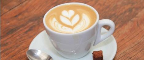 Imagem em close up. Xícara cheia de café com leite, toda branca sobre um pires da mesma cor, uma pequena colher prateada e um biscoitinho sobre ele. Na superfície bege, um delicado desenho de coração ornamentado, feito com creme branco.