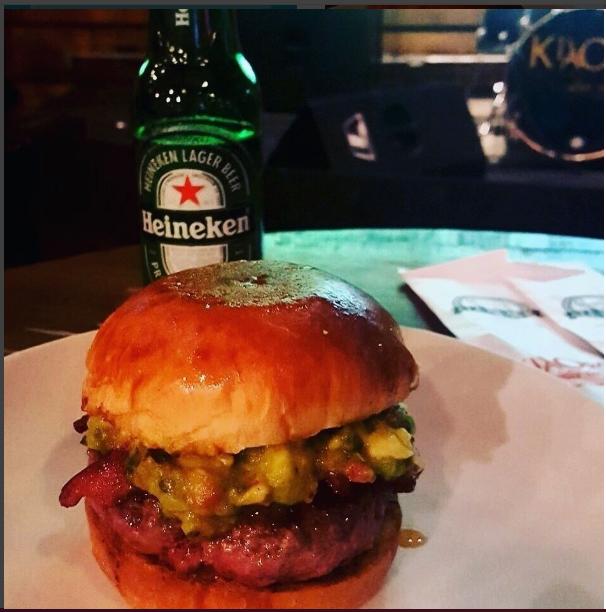 Foto en primer plano de un sándwich de salchicha a la parrilla con queso en un pan redondo. Detrás, una botella verde de la cerveza Heineken.