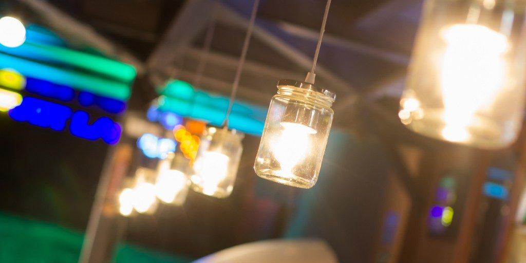 Foto em close up. Várias luminárias estilizadas – potes de vidro com uma lâmpada acesa dentro e tampa de metal, penduradas lado a lado por um fio preso ao teto.