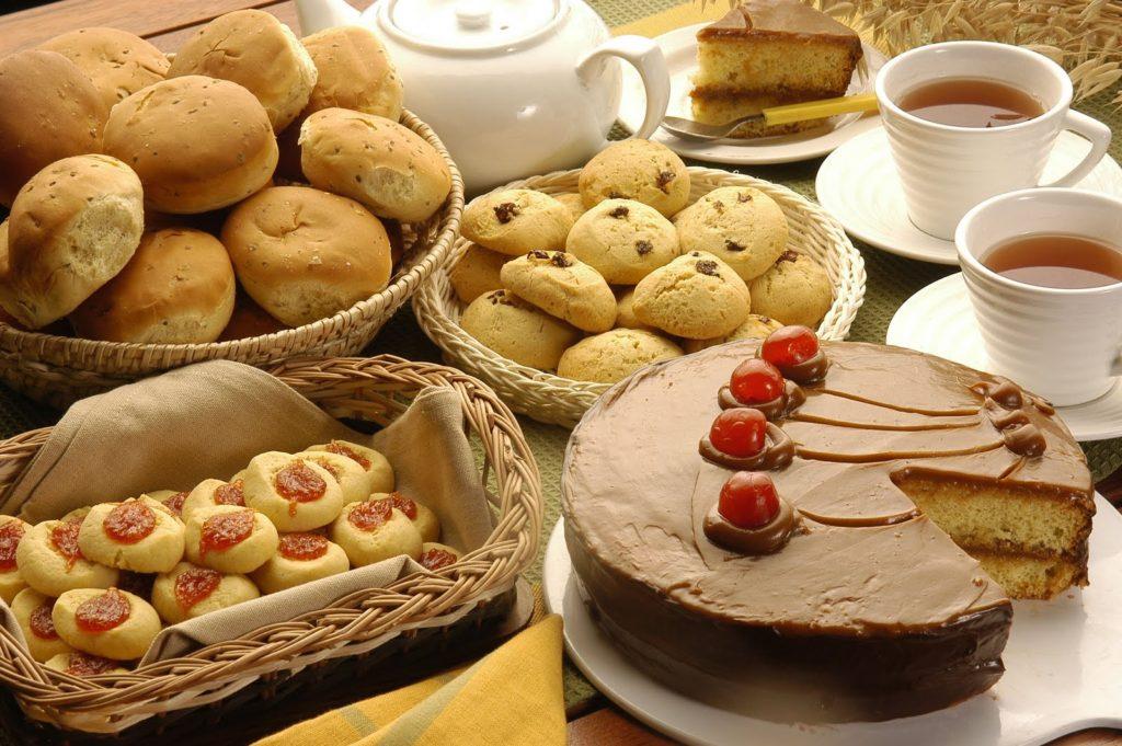 Sobre uma mesa de madeira, à esquerda, uma cesta com pães de batata e outra com biscoitos cobertos por geléia de goiaba. No centro, um bule branco de chá, uma cesta de bolinhos e um grande bolo coberto de chocolate com cerejas. À direita, um pratinho branco com uma fatia de bolo de chocolate e duas xícaras brancas cheias de chá.