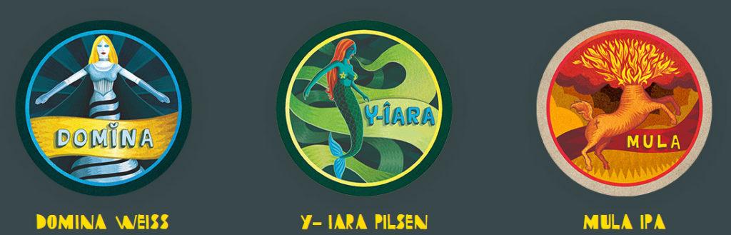 """Sobre um fundo verde escuro, 3 apoios para copos de cerveja (bolachas de chopp), cada um trazendo um desenho que representa o tipo e a marca das cervejas. Da esquerda para a direita, o 1º é composto pela figura de uma mulher com cabelos longos e amarelos, trajando luvas e um vestido longo em tons de azul claro e escuro, além da palavra """"Domina"""" sobre uma faixa amarela. Abaixo, em letras amarelas, a indicação """"DOMINA WEISS"""". O 2º é composto pela figura de uma sereia em tons de verde claro e escuro e cabelos alaranjados. Ao lado da cauda, a palavra """"Y-IARA"""" sobre uma fixa verde. Abaixo, em letras amarelas, a indicação """"Y-IARA PILSEN"""". O 3º é composto pela figura de uma mula sem cabeça com labaredas de fogo saindo pelo pescoço e a palavra """"MULA"""", tudo em tons de vermelho forte, laranja e amarelo. Abaixo, em letras amarelas, a indicação """"MULA IPA""""."""
