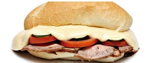 Imagem em close up de um sanduíche com queijo derretido, rodelas de tomate e fatias de rosbife, no pão francês.