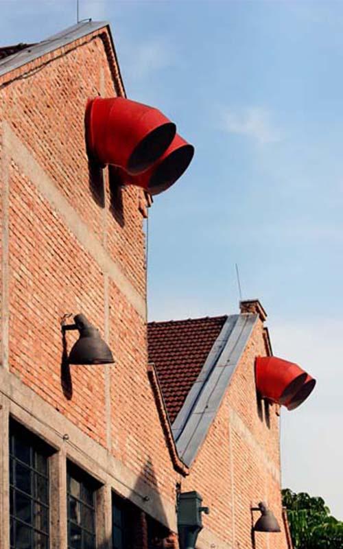 Parte superior da fachada de tijolos aparentes pertencente a uma antiga fábrica. Em destaque, 2 telhados lado a lado no formato de uma letra M. Na ponta de cima em ambos, saem 2 largos tubos vermelhos de ventilação, curvados para baixo.