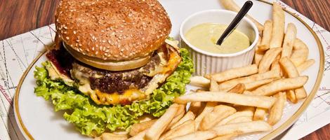Em um grande prato branco e ovalado, 1 sanduíche com pão redondo, hambúrguer e queijo sobre folhas de alface, uma porção de batatas fritas e um pequeno pote com maionese.