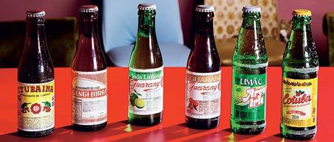 6 garrafas pequenas de refrigerante sobre uma mesa vermelha.