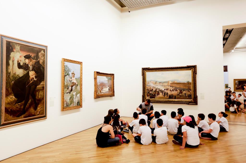 Salão de exposições com paredes brancas, onde estão pendurados 4 grandes quadros. O piso é de madeira clara, onde está sentado um grupo de jovens e um adulto palestrante. Ao fundo e a direita, parte de outra sala idêntica onde se encontra outro grupo de jovens.
