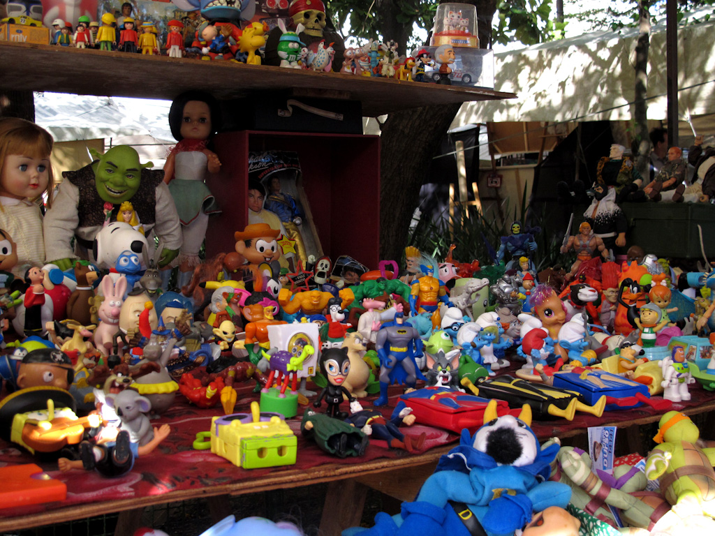 Cientos de muñecos de juguete de los más variados colores, materiales y tamaños como Snoopy, Shrek, Chico Bento, Batman, etc, expuestos en una gran mesa de madera.