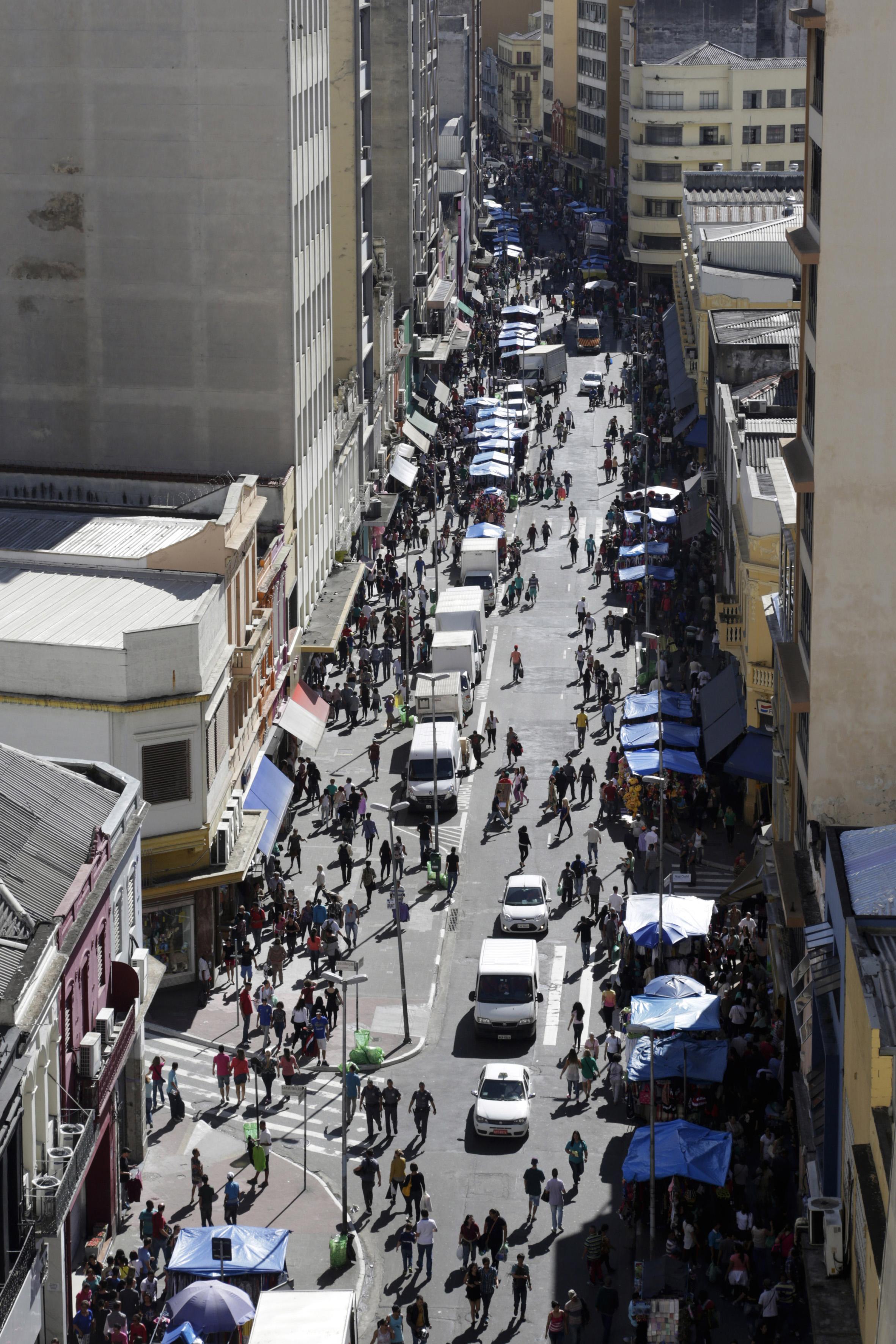 Imagen de lo alto de una calle de comercio popular, rodeada por numerosos edificios con tiendas en la planta baja. En el centro, calle dividida entre vehículos y decenas de barracas de lona azul repletas de mercancías variadas, lado a lado bordeando las aceras, donde cientos de personas caminan.