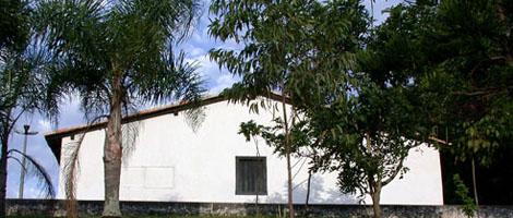 Imagem lateral de uma pequena casa toda branca, possui uma janela gradeada de madeira azul marinho bem no centro. Na parte externa, várias árvores de médio e grande porte.