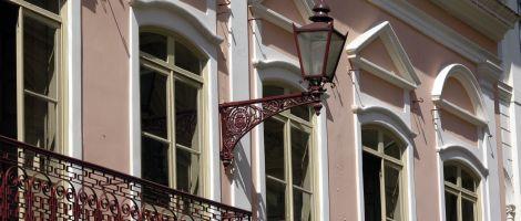 Fachada superior do casarão, toda em cor de rosa claro. Destacam-se 5 janelões com molduras brancas em alto relevo. A parte de cima é curvada e, acima deles, elementos arquitetônicos decorativos em forma de triângulo, também na cor branca. Entre duas janelas, destaca-se uma antiga luminária no formato de um lampião, presa à parede por um longo braço de ferro todo trabalhado, tudo na cor de vinho. À esquerda, na frente da 1ª janela, parte da grade de uma pequena sacada, toda em ferro cor de vinho minuciosamente trabalhado.